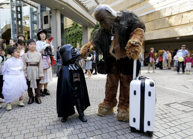"Cosplayers dressed as Star Wars characters Chewbacca (R) and Darth Vader talk at a Star Wars Day fan event in Tokyo May 4, 2015. Star Wars fans celebrate May 4 as Star Wars Day, a pun that comes from an iconic quote in the movie, ""May the Force be with you"". (Photo by Toru Hanai/Reuters)"