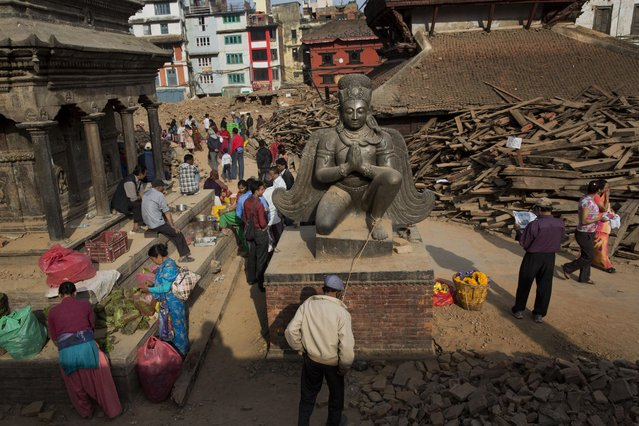 Nepalese gather around Basantapur Durbar Square, damaged in the April 25 earthquake in Kathmandu, Nepal, Tuesday, May 5, 2015. (Photo by Bernat Amangue/AP Photo)