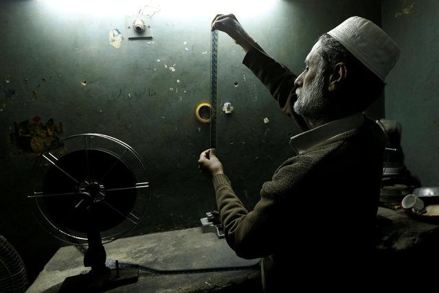 A worker checks a film strip at a cinema house in Peshawar, Pakistan February 21, 2019. (Photo by Fayaz Aziz/Reuters)