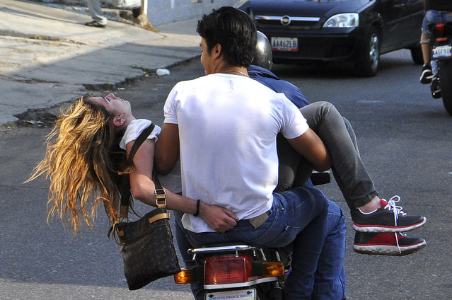 Opposition supporter Genesis Carmona is evacuated on a motorcycle after being shot in the head during a protest against Nicolas Maduro's government in Valencia, some 100 miles (160 km)  from Caracas, February 18, 2014. (Photo by Mauricio Centeno-Notitarde/Reuters)