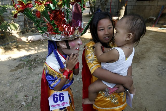 "Penitent Jerry Mazon, 9, wears his ""Morions"" mask while playing with his baby brother during Holy Week celebrations in Mogpog, Marinduque in central Philippines March 22, 2016. (Photo by Erik De Castro/Reuters)"