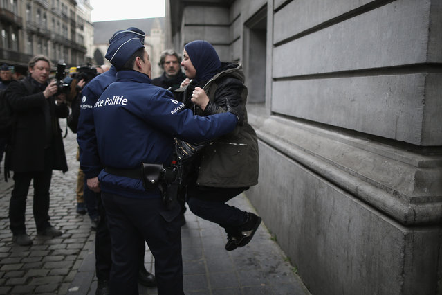 Police officers placate a woman as emotions run high after people observed a one minute silence at the Place De La Bourse in honour of the victims of yesterdays' terror attacks on March 23, 2016 in Brussels, Belgium. Belgium is observing three days of national mourning after 34 people were killed in a twin suicide blast at Zaventem Airport and a further bomb attack at Maelbeek Metro Station. Two brothers are thought to have carried out the airport attack and an international manhunt is underway for a third suspect. The attacks come just days after a key suspect in the Paris attacks, Salah Abdeslam, was captured in Brussels. (Photo by Christopher Furlong/Getty Images)