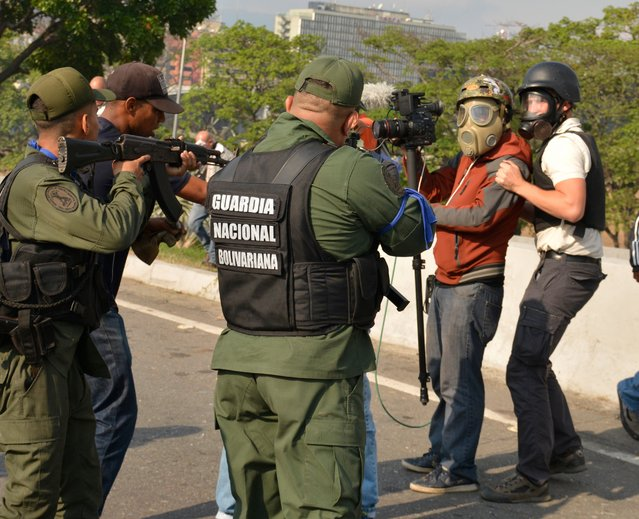 Pro-Guaidó soldiers point their weapons towards a cameraman in the outskirts of the air force base La Carlota on April 30, 2019 in Caracas, Venezuela. Through a live broadcast via social media, Venezuelan opposition leader Juan Guaido called for a military uprising against the government of Nicolás Maduro. He declared to be at the air base of La Carlota and was seen surrounded by soldiers and opposition activist Leopoldo Lopez, who was under house arrest. (Photo by Rafael Briceno/Getty Images)