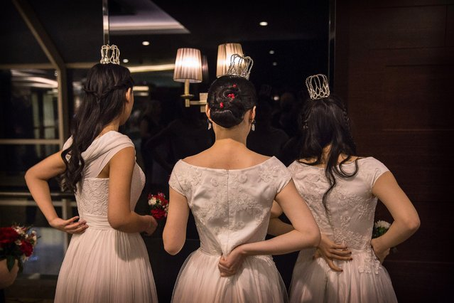 Debutantes from a local academy adjust their outfits before taking part in the Vienna Ball at the Kempinski Hotel, March 19, 2016, in Beijing. (Photo by Kevin Frayer/Getty Images)