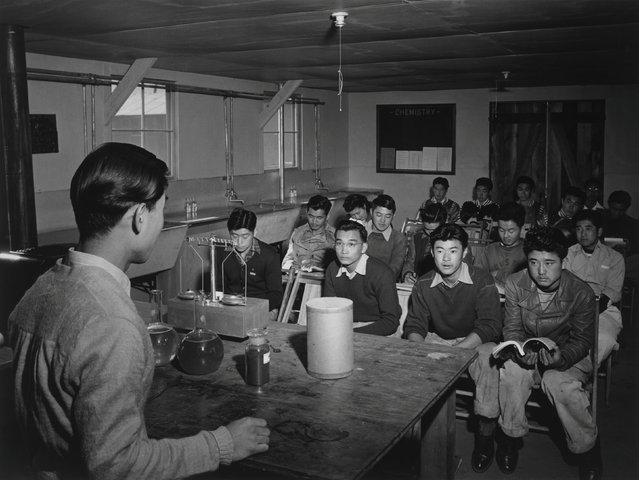 Students seated in a classroom laboratory listen to a science instructor at the Manzanar War Relocation Center in California, in this 1943 handout photo. (Photo by Courtesy Ansel Adams/Library of Congress, Prints and Photographs Division/Reuters)