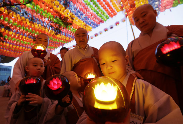 Shaven-headed boys hold lanterns during a lighting ceremony to celebrate Buddha's upcoming birthday on May 25 at the Jogye Temple in Seoul, South Korea Wednesday, May 13, 2015. Nine children entered the temple to have an experience of monks' life for two weeks. (Photo by Ahn Young-joon/AP Photo)
