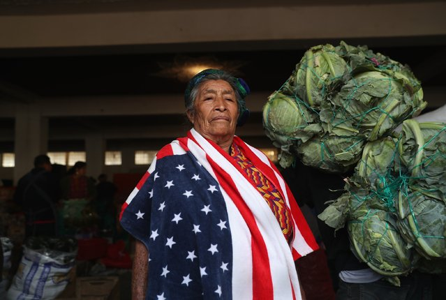 Maria Isabel Luna, 75, wears an American towel for warmth over her traditional Mayan dress while working at a vegetable market on February 11, 2017 in Almolonga, Guatemala.  She said that two of her family members work as immigrant laborers in Los Angele. (Photo by John Moore/Getty Images)