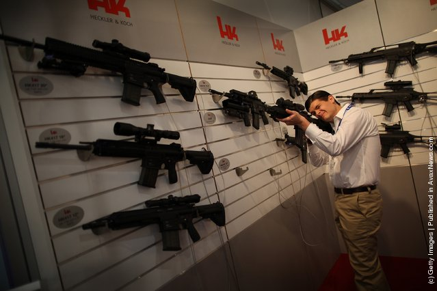 A visitor tries out a Heckler and Koch assault rifle at the Defence and Security Exhibition