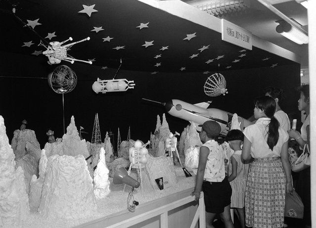 """Japanese children press close to view an """"outer world"""" space exhibit in a Tokyo department store on August 19, 1958. There they saw a rocket which landed on the surface of the moon, strange looking people of the moon walking around, and even a satellite going around the moon. (Photo by AP Photo via The Atlantic)"""