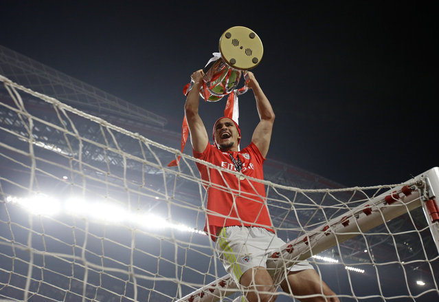 Benfica goalkeeper Ivan Zlobin holds the trophy atop the goal after the Portuguese league last round soccer match between Benfica and Santa Clara at the Luz stadium in Lisbon, Saturday, May 18, 2019. Benfica won 4-1 to clinch the championship title. (Photo by Armando Franca/AP Photo)