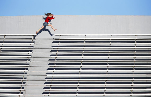 Mekenzie Blanchard, 7, of Tulsa jumps from one side of the bleachers to the other during a soccer game at S.E. Williams Stadium at Booker T. Washington High School on Monday, March 10, 2014. (Photo by Tom Gilbert/AP Photo/Tulsa World)