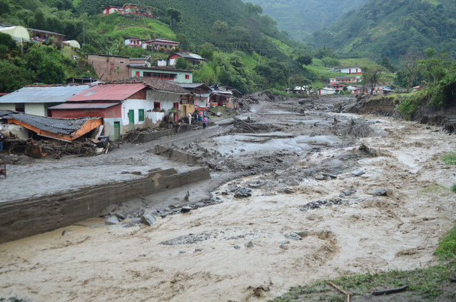 An overflooded ravine cuts through Salgar, in Colombia's northwestern state of Antioquia, Tuesday, May 19, 2015, where a deadly flood and mudslide swept through a day earlier. (Photo by Luis Benavides/AP Photo)