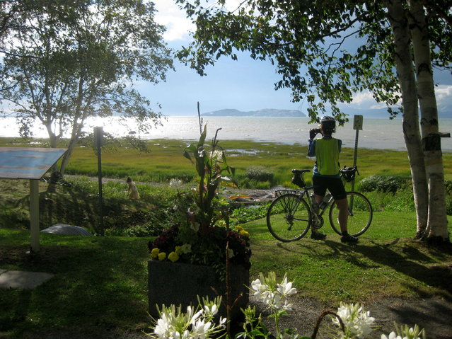A cyclist takes in the St. Lawrence vista at Notre-Dame-du-Portage, Quebec, on Aug. 12, 2015. Along the south shore of the St. Lawrence River in this area of around Kamouraska, the panorama of river, sky, flowers and gardens defines the magic of bicycling the Route Verte network in Quebec. (Photo by Cal Woodward/AP Photo)