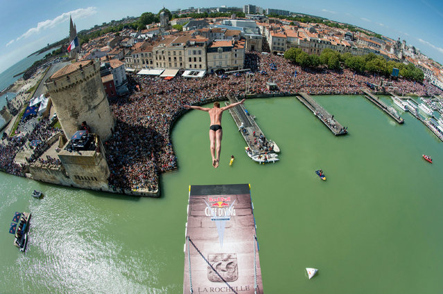 A handout photo received from Red Bull and taken on May 17, 2015 shows Artem Silchenko of Russia diving from the 27.5 metre platform on the Saint Nicolas Tower during the second stop of the Red Bull Cliff Diving World Series at La Rochelle, France. Gary Hunt of the UK won the event, with fellow Briton Blake Aldridge placing second and Orlando Duque of Colombia third. (Photo by Vincent Curutchet/AFP Photo)