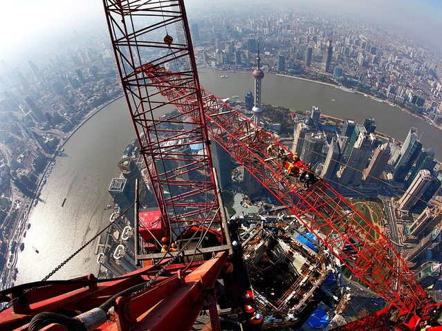 "Construction workers have been able to scale the half-mile £1.6billion monolith in the world's longest lift. Principal architect Jun Xia said it serves ""as a stunning representation of our past, our present and China's boundless future"". (Photo by Rex Features)"