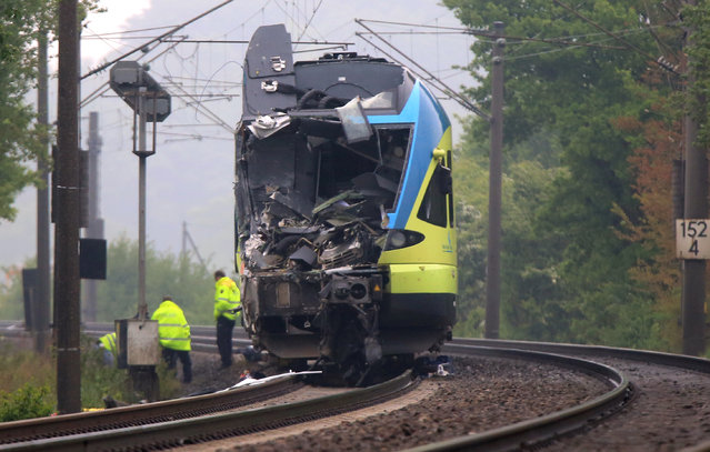 Workers are busy near the damaged train that hit a truck on a road crossing near Ibbenbueren, western Germany, Saturday, May 16, 2015. Police said two people have been killed and at least 20 others were injured in the accident. (Photo by Marcel Kusch/AP Photo/DPA)
