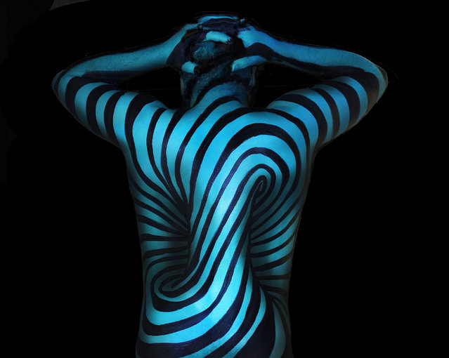 A talented body painter has created a series of mind-bending illusions that cover entire torsos. Natalie Fletcher's work are enough to make people double-take, the spiraling patterns of some appearing to fade into the abyss. In other works, the artists designs look as though they are never ending, while some show body parts appearing to protrude from models chests. The idea behind the ongoing series came to Natalie, 30, as a means of keeping entertained during the winter months. Here: Optical illusion bodypaint. (Photo by Natalie Fletcher/Cater News)