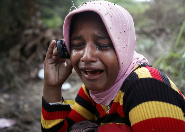 "In this Friday, May 22, 2015 photo, Rohingya migrant Sahiza Begum weeps as she talks on the phone with her brother who resides in Malaysia at a temporary shelter in langsa, Aceh province, Indonesia. ""The vulnerability of these children can never be overstated"", said Steve Hamilton, deputy chief of mission at the International Organization for Migration in Indonesia, adding that the government has said special care will be provided to ensure the safety of unaccompanied children. (Photo by Binsar Bakkara/AP Photo)"
