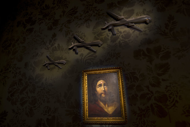 "A wall decorated with models of drones and a painting of Jesus with a sniper's dot on his forehead is seen in the ""The Walled Off Hotel"" in the West Bank city of Bethlehem, Friday, March 3, 2017. (Photo by Dusan Vranic/AP Photo)"