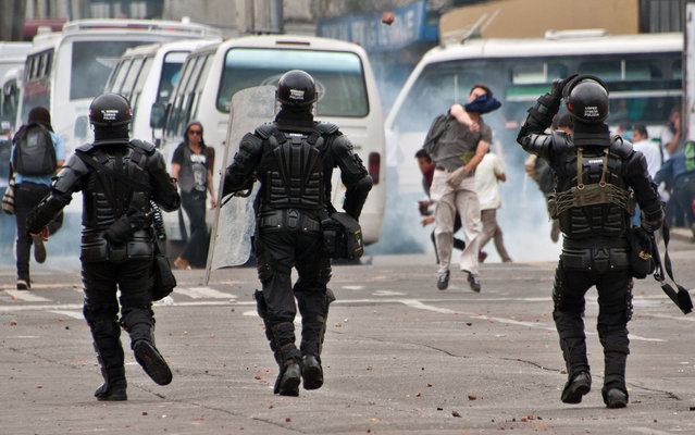 A student of the Pedagogical University (2-R) throws stones at the riot police during a protest demanding government to improve the quality of public education, in Bogota, Colombia, on March 27, 2014. (Photo by Guillermo Legaria/AFP Photo)