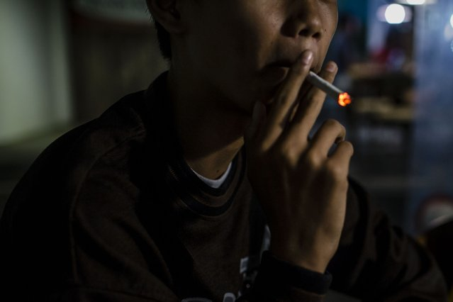 Anggit (14), smokes at a coffee shop with his friends on March 7, 2017 in Yogyakarta, Indonesia. (Photo by Ulet Ifansasti/Getty Images)