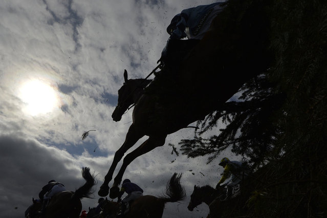 """Riders and horses clear """"The Chair"""" in the """"Supporting The Everton In The Community Steeple Chase"""" during the Grand National horse racing meeting at Aintree, northern England April 4, 2014. (Photo by Toby Melville/Reuters)"""