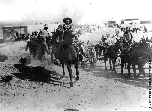 Mexican revolutionary leader General Pancho Villa (1878 - 1923) rides at the head of the Mexican rebels during the Mexican Revolution