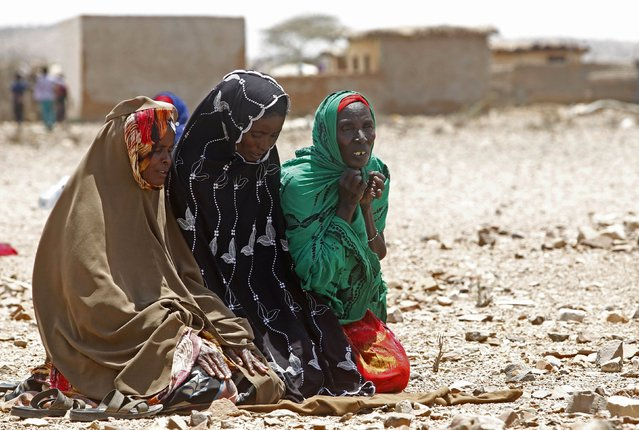 Women pray as they wait for assistance at Hariirad town of Awdal region, Somaliland April 9, 2016. Across the Horn of Africa, millions have been hit by the severe El Nino-related drought. In Somaliland and its neighbouring, also semi-autonomous, Puntland region, 1.7 million people are in need of aid, according to the United Nations. In Somaliland itself, the most affected areas include the northwest Awdal region bordering Ethiopia. (Photo by Feisal Omar/Reuters)