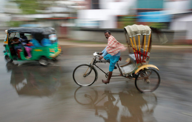 A man pedals his cycle rickshaw during rains in Agartala, India, March 18, 2017. (Photo by Jayanta Dey/Reuters)