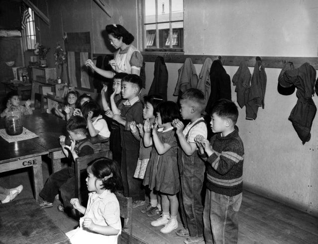 In this May 1943 file photo, Aiko Sumoge, an assistant teacher, leads a kindergarten class in singing an English folk song at the internment relocation center for Japanese Americans in Tulelake, Calif., during World War II. Beliefs that Hispanics and Asians living in the U.S. won't assimilate or refuse to speak English are based on stereotypes that scholars say are linked to notions of white supremacy. Throughout American history, Hispanics and Asians have been pressured to adopt the customs of the mainstream white population. The pressure came even as some laws forbade them from voting, intermarrying and having access to education and public facilities. (Photo by AP Photo/File)