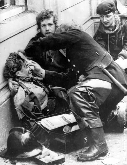 Firemen tend to a wounded victim of an Irish Republican Army car bomb explosion in Donegal Street, Belfast. The blast killed 6 people and injured 146