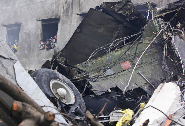 Residents examine the wreckage of an Indonesian Air Force cargo plane from a building next to the site where it crashed in Medan, North Sumatra, Indonesia, Tuesday, June 30, 2015. (Photo by Binsar Bakkara/AP Photo)