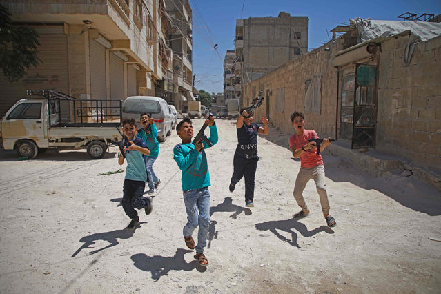 Syrian boys play with plastic guns on the first day of the Muslim religious festival of Eid al-Adha in al-Dana in Syria's rebel-controlled Idlib region, near the border with Turkey, on August 11, 2019. Muslims across the world are celebrating the first day of the Feast of Sacrifice, which marks the end of the hajj pilgrimage to Mecca and commemorates prophet Abraham's sacrifice of a lamb after God spared Ishmael, his son. (Photo by Aaref Watad/AFP Photo)