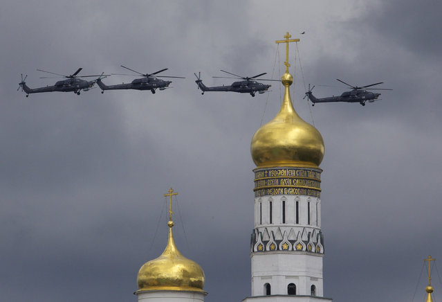 Russian military helicopters fly over Ivan the Great bell-tower and Moscow's Kremlin during a general rehearsal for the Victory Day military parade which will take place at Moscow's Red Square on May 9 to celebrate 71 years after the victory in WWII in Moscow, Russia, on Thursday, May 5, 2016. (Photo by Ivan Sekretarev/AP Photo)