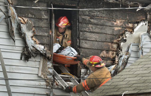Syracuse firefighters remove a body through an upstairs window at the scene of a fatal fire Friday May 6, 2016 in Syracuse, N.Y. The blaze was reported early Friday morning.  When firefighters arrived just minutes after receiving a 911 call, the front of the house was engulfed in flames, officials said. (Photo by David Lassman/The Syracuse Newspapers via AP Photo)