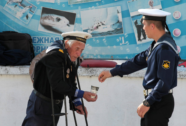 A Russian navy serviceman gives alms to a beggar on an embankment of the Black Sea port of Sevastopol, Crimea, May 8, 2016. (Photo by Pavel Rebrov/Reuters)
