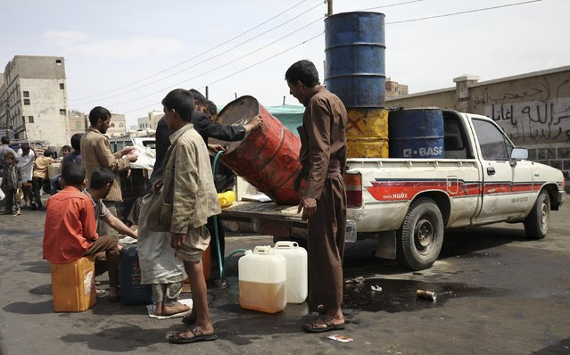 A man sells black market fuel amid an acute shortage of fuel in Sanaa, Yemen, July 1, 2015. (Photo by Mohamed al-Sayaghi/Reuters)