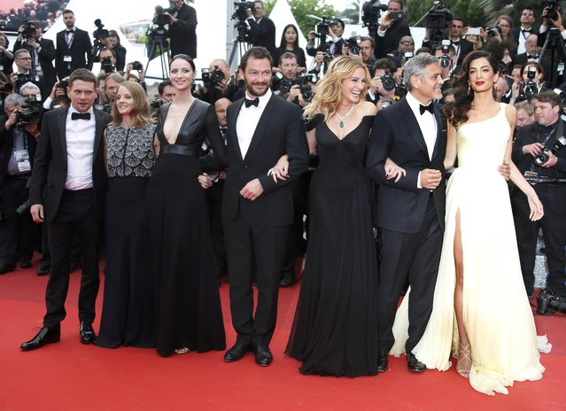 """(L-R) Cast member Jack O'Connell, director Jodie Foster, cast members Caitriona Balfe, Dominic West, Julia Roberts, George Clooney and his wife Amal Alamuddin pose on the red carpet as they arrive for the screening of the film """"Money Monster"""" out of competition at the 69th Cannes Film Festival in Cannes, France, May 12, 2016. (Photo by Eric Gaillard/Reuters)"""