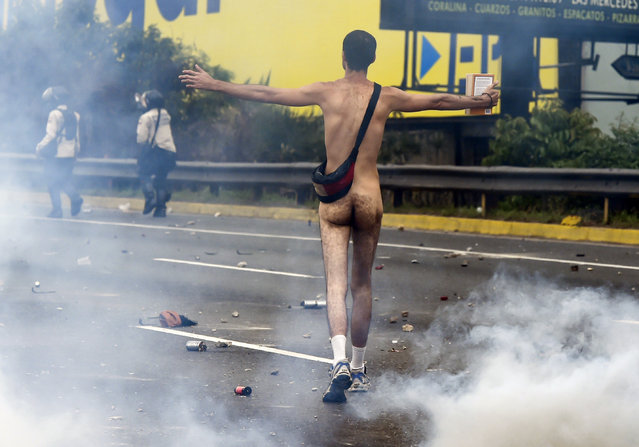 A naked demonstrator remonstrates with riot police during a protest against Venezuelan President Nicolas Maduro, in Caracas on April 20, 2017. (Photo by Juan Barreto/AFP Photo)