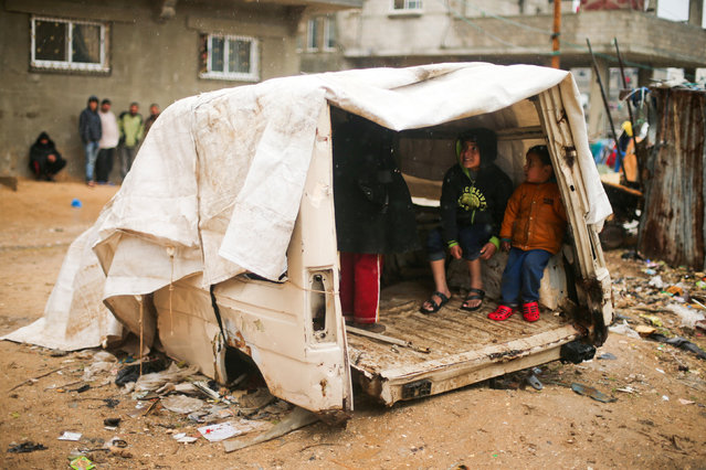 Palestinian boys take cover in the remains of a vehicle during heavy rain in a neighbourhood in the northern Gaza Strip February 16, 2017. (Photo by Mohammed Salem/Reuters)