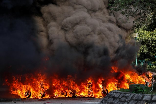 Motorbikes are on fire after they were hit with a molotov cocktail during a protest on China's National Day, in Wong Tai Sin, Hong Kong, China on October 1, 2019. (Photo by Tyrone Siu/Reuters)