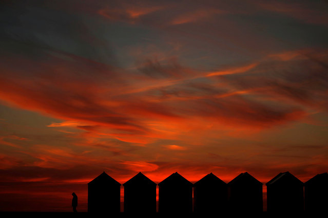 A man enjoys the sunset beside beach cabins on a pebbled beach in Cayeux-sur-Mer, France, May 13, 2019. (Photo by Pascal Rossignol/Reuters)