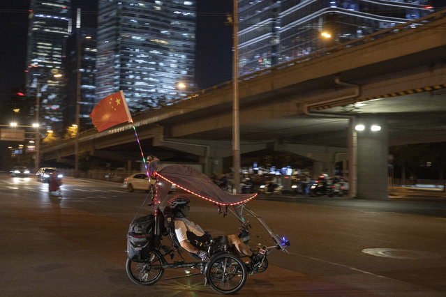 In this Wednesday, September 25, 2019, photo, a cyclists with a Chinese national flag rides through the Central Business District in Beijing. Patriotic banners, elaborate flower displays and tightened security are all on tap as the Chinese capital prepares to mark the 70th anniversary of Communist Party rule on Tuesday, Oct. 1, 2019. (Photo by Ng Han Guan/AP Photo)