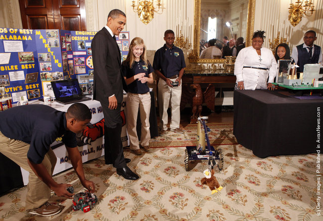 U.S. President Barack Obama (2L) watches a robot with Robert Knight III (L), Morgan Ard (3L) and Titus Walker (C), eighth-grade students at Monroeville Jr. High School in Monroeville, Alabama, who won high honors at the South BEST robotics competition, while touring student science fair projects on exhibit in the State Dining Room at the White House