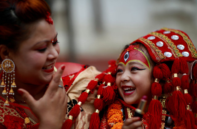 A young girl dressed as the Living Goddess Kumari smiles as she speaks with her mother during the Kumari Puja festival, in which young girls pose as the Living Goddess Kumari and are worshipped by people in belief that their children will remain healthy, in Kathmandu, Nepal on September 11, 2019. (Photo by Navesh Chitrakar/Reuters)