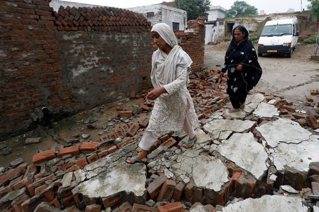 Women walk over rubbles of a damaged wall after an earthquake in Jatlan, Mirpur, Pakistan, September 25, 2019. (Photo by Akhtar Soomro/Reuters)