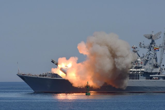 Missiles are fired by a Russian navy battleship during a rehearsal of the Russian Navy Day parade in Sevastopol, Crimea, Friday, July 24, 2015. (Photo by Alexander Polegenko/AP Photo)