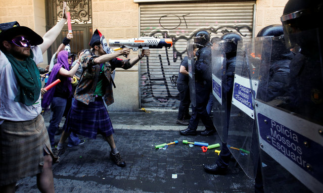 "A protester squirts a water gun at Catalan regional police in full riot gear during a protest over the eviction of squatters earlier in the week from ""The Expropriated Bank"", in Barcelona, Spain, May 29, 2016. (Photo by Albert Gea/Reuters)"