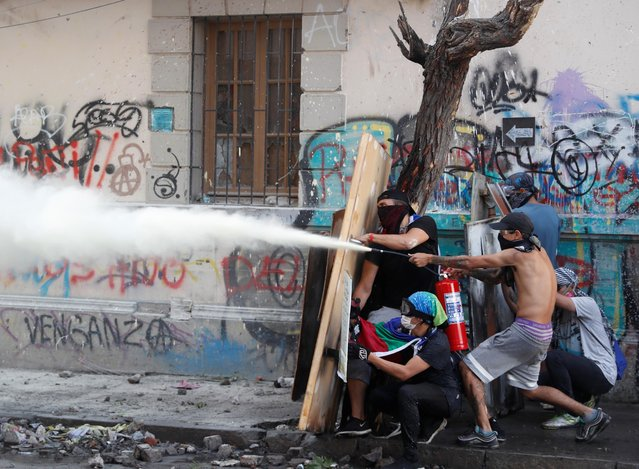 Demonstrators use improvised shields and a fire extinguisher during a protest against Chile's government in Santiago, Chile on November 19, 2019. (Photo by Goran Tomasevic/Reuters)