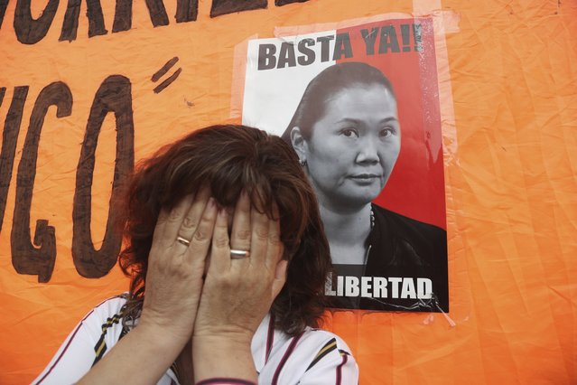 """A supporter of jailed opposition leader Keiko Fujimori cries next to a poster with her image with text that reads in Spanish """"Enough!"""" and """"freedom,"""" outside of the women's prison in Lima, Peru, Monday, November 25, 2019. Peru's Constitutional Tribunal has approved a habeas corpus request to free Fujimori. (Photo by Martin Mejia/AP Photo)"""